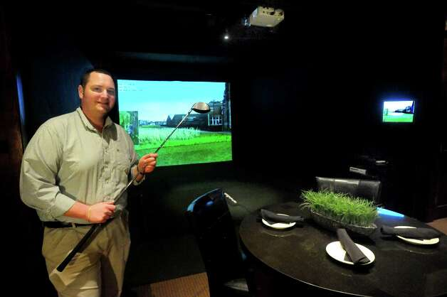 Tom Feola, general manager of Brookfield Indoor Golf Club at Maggie McFly's, stands by one of the golf simulators Thursday, Nov. 30, 2012. Photo: Michael Duffy / The News-Times