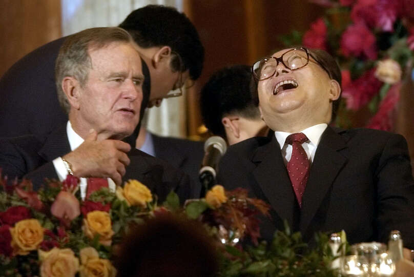 Former President George Bush and Chinese President Jiang Zemin share a laugh during a dinner in Hous