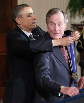 President Barack Obama presents former President George H.W. Bush the 2010 Medal of Freedom during a ceremony in the East Room of the White House in Washington. Photo: Pablo Martinez Monsivais, AP / AP