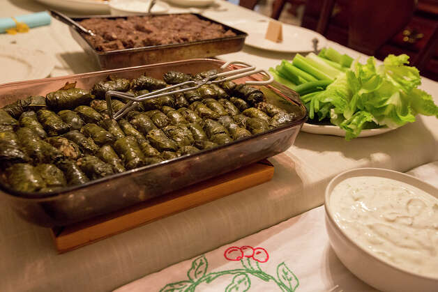 Yabrak, grape leaves stuffed with meat, onion, rice and Syrian Pepper, center, along with kibbi, meat with onion, burghul, pine nuts and Syrian Pepper, lettuce and celery, middle right, and khyar bil-laban, or yogurt with garlic, cucumber, mint and sour cream, are pictured during an international supper club at the home of Joe and Lyne Jackson on Saturday, Nov. 24, 2012. Burghul is cracked wheat and Syrian Pepper is made of allspice and other spices. MICHAEL MILLER / FOR THE EXPRESS-NEWS Photo: Michael Miller, San Antonio Express-News / © San Antonio Express-News