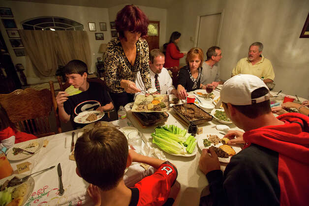 Lyne Jackson, center, makes a plate of food during an international supper club at her home on Saturday, Nov. 24, 2012. MICHAEL MILLER / FOR THE EXPRESS-NEWS