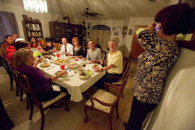 Lyne Jackson, right, takes a picture of the dinner group during an international supper club at her home on Saturday, Nov. 24, 2012. MICHAEL MILLER / FOR THE EXPRESS-NEWS