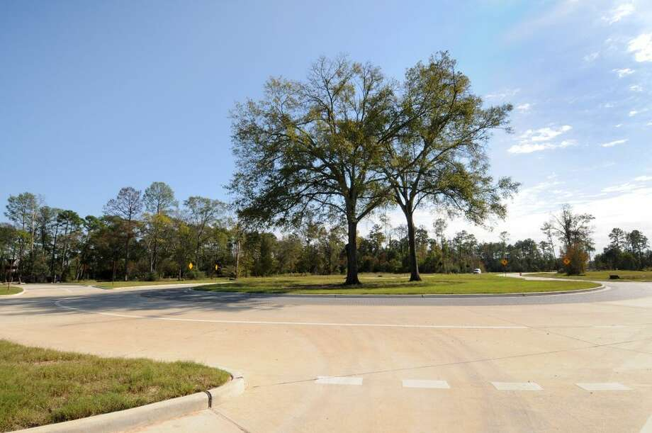 A view looking south of the traffic roundabout at Energy Drive and East Mossy Oaks Road with two of the community's oak trees. (CDC Houston)