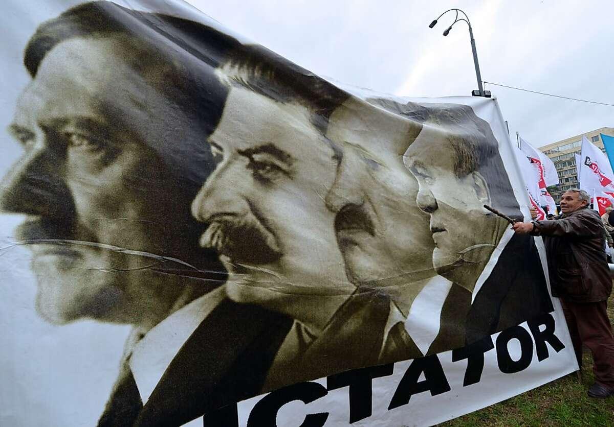 A man holds a placard depicting Adolf Hitler, Josef Stalin, Belarus President Alexander Lukashenko and Ukrainian President Viktor Yanukovych and reading