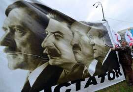 "A man holds a placard depicting Adolf Hitler, Josef Stalin, Belarus President Alexander Lukashenko and Ukrainian President Viktor Yanukovych and reading""Dictator"" during a rally of the opposition in front of the central election commission in Kiev on November 5, 2012. Thousands of Ukrainians massed in central Kiev on November 5 to protest against alleged fraud in parliamentary elections won by the ruling party as the opposition threatened not to recognise the new legislature. At least 2,000 opposition supporters carrying Ukrainian flags gathered outside the headquarters of the central election commission amid a heavy presence of elite Berkut anti-riot police, an AFP correspondent said. AFP PHOTO/ SERGEI SUPINSKYSERGEI SUPINSKY/AFP/Getty Images"