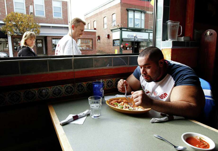 In this photo taken, Friday, Nov. 16, 2012, Egyptian Body builder Moustafa Ismail eats lunch at his favorite Mexican restaurant after his daily workout at World Gym in Milford, Mass. Ismail has been given the title of world's biggest arms, biceps and triceps, by the Guinness Book of World Records. Photo: Stephan Savoia, AP / AP