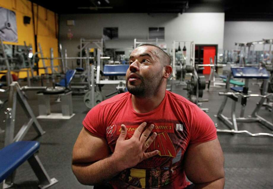In this photo taken, Friday, Nov. 16, 2012, Egyptian Body builder Moustafa Ismail takes a breather during his daily workout at World Gym in Milford, Mass. Ismail has been given the title of world's biggest arms, biceps and triceps, by the Guinness Book of World Records. Photo: Stephan Savoia, AP / AP