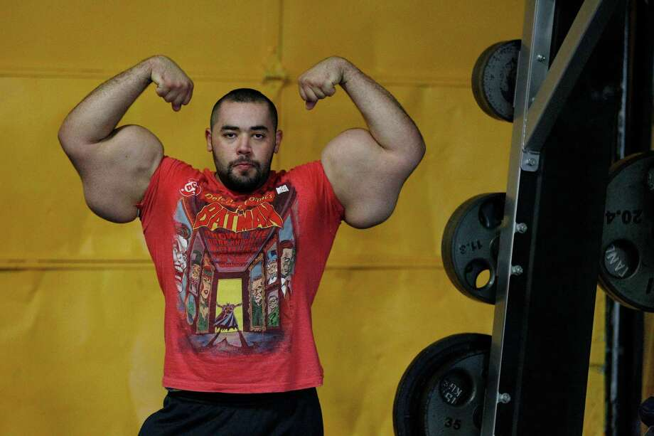 In this photo taken, Friday, Nov. 16, 2012, Egyptian Body builder Moustafa Ismail poses during his daily workout at World Gym in Milford, Mass. Ismail has been given the title of world's biggest arms, biceps and triceps, by the Guinness Book of World Records. Photo: Stephan Savoia, AP / AP