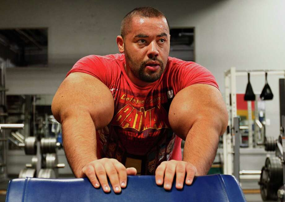 In this photo taken, Friday, Nov. 16, 2012, Egyptian Body builder Moustafa Ismail rests during his daily workout at World Gym in Milford, Mass. Ismail has been given the title of world's biggest arms, biceps and triceps, by the Guinness Book of World Records. Photo: Stephan Savoia, AP / AP