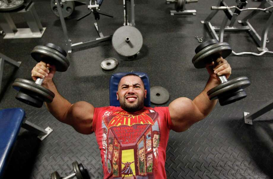 In this photo taken, Friday, Nov. 16, 2012, Egyptian Body builder Moustafa Ismail lifts weights during his daily workout at World Gym in Milford, Mass. Ismail has been given the title of world's biggest arms, biceps and triceps, by the Guinness Book of World Records. Photo: Stephan Savoia, AP / AP