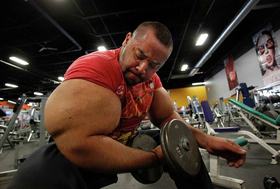 In this photo taken, Friday, Nov. 16, 2012, Egyptian Body builder Moustafa Ismail lifts free weights during his daily workout at World Gym in Milford, Mass. Ismail has been given the title of world's biggest arms, biceps and triceps, by the Guinness Book of World Records. Photo: Stephan Savoia, AP / AP