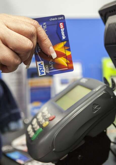 A consumer pays with a US Bank VISA debit card, as she shops for Thanksgiving celebrations  at the Pre-Black Friday event at the Walmart Supercenter store in Rosemead, Calif., Wednesday, Nov. 21, 2012. (AP Photo/Damian Dovarganes) Photo: Damian Dovarganes, Associated Press