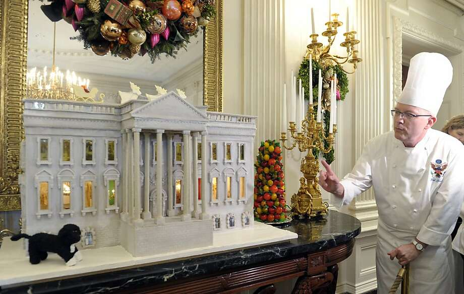 The Obamas' home, sweet home: White House pastry chef Bill Yosses shows off his nearly 300-pound gingerbread White House in the State Dining Room of the White House in Washington. The house features an out-of-scale Bo, a vegetable garden and interior views. And it's conveniently perched on the edge of a non-fiscal cliff. Photo: Susan Walsh, Associated Press