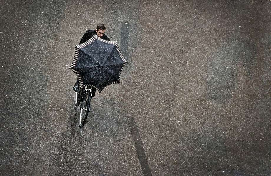 A bicyclist shields himselffrom the falling snow with an umbrella in Munich - or maybe he's using it as a sail. Photo: Victoria Bonn-meuser, AFP/Getty Images