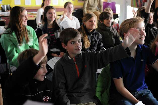 "Students in Kristen Ball's fifth-grade class at New Canaan Country School wave to students in Tanzania during an attempt at video-chatting with the African students. Due to a lack of reliant electricity the Tanzanian class had difficulty connecting to the internet, so brief waves were all that the students could share on Thursday, November 29, 2012. The American students translated questions for the Tanzanian students into Swahili and practiced speaking the language while they waited. Student Molly Connors said she was a little disappointed they didn't get to chat this time but the experience taught a lesson. ""Well, I mean, it was a little disappointing but we also got to learn how they feel on the other end too, because this doesnâÄôt usually get to happen for them and itâÄôs lucky that we get to talk to them,"" she said. Photo: Lindsay Niegelberg / Stamford Advocate"