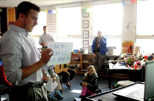 "New Canaan Country School fifth-grade apprentice teacher Danny Seymour holds up a sign that reads ""Can you hear us? We hear you,"" during an attempt at video-chatting with students in Tanzania. Due to a lack of reliant electricity the Tanzanian class had difficulty connecting to the internet, so brief waves to each other were all that the students could share on Thursday, November 29, 2012. The American students translated their questions into Swahili and practiced speaking the language while they waited. Student Molly Connors said she was a little disappointed they didn't get to chat this time but the experience taught a lesson. ""Well, I mean, it was a little disappointing but we also got to learn how they feel on the other end too, because this doesnâÄôt usually get to happen for them and itâÄôs lucky that we get to talk to them,"" she said. Photo: Lindsay Niegelberg / Stamford Advocate"