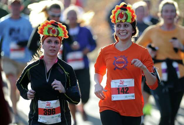 Caitlyn Ruble, of Fairfield, left, and Christen Ruble, of New York, NY, run in the 35th annual Pequot Runners Thanksgiving Day Five-Mile Race Thursday, Nov. 22, 2012 in Fairfield, Conn. Photo: Autumn Driscoll / Connecticut Post