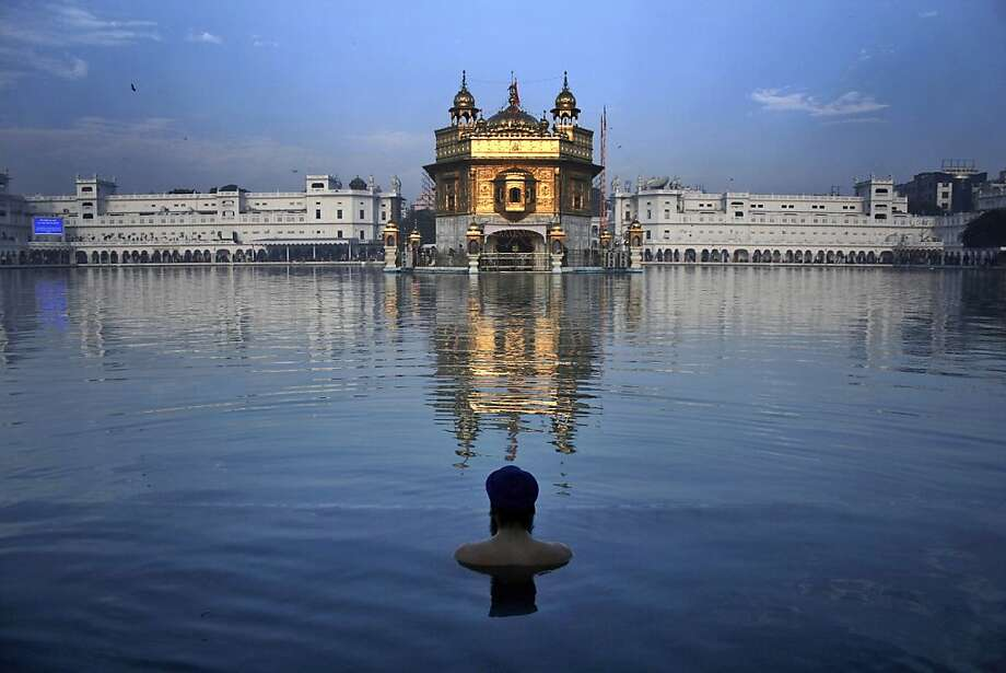 Birthday bath: A Sikh devotee takes a holy dip in the sacred pond of the Golden Temple, Sikh's holiest temple, on the birth anniversary of Guru Nanak in Amritsar, India. Nanak broke away from Hinduism, India's dominant religion, by preaching equality of the races and genders, and rejecting image worship and the caste system. Photo: Sanjeev Syal, Associated Press