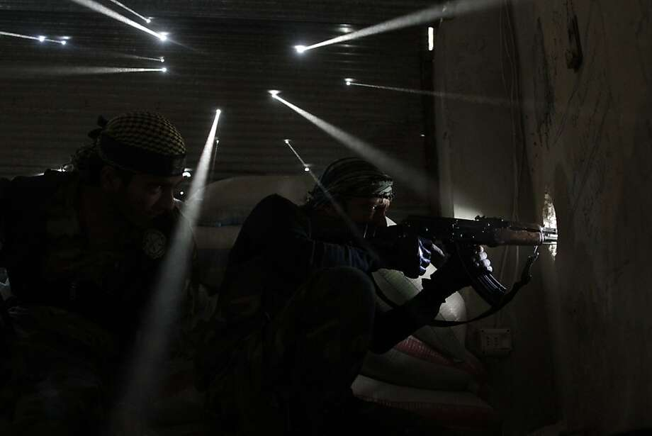 Two Syrian rebels take sniper positions at the heavily contested neighborhood of Karmal Jabl, central Aleppo. Photo: Javier Manzano, AFP/Getty Images
