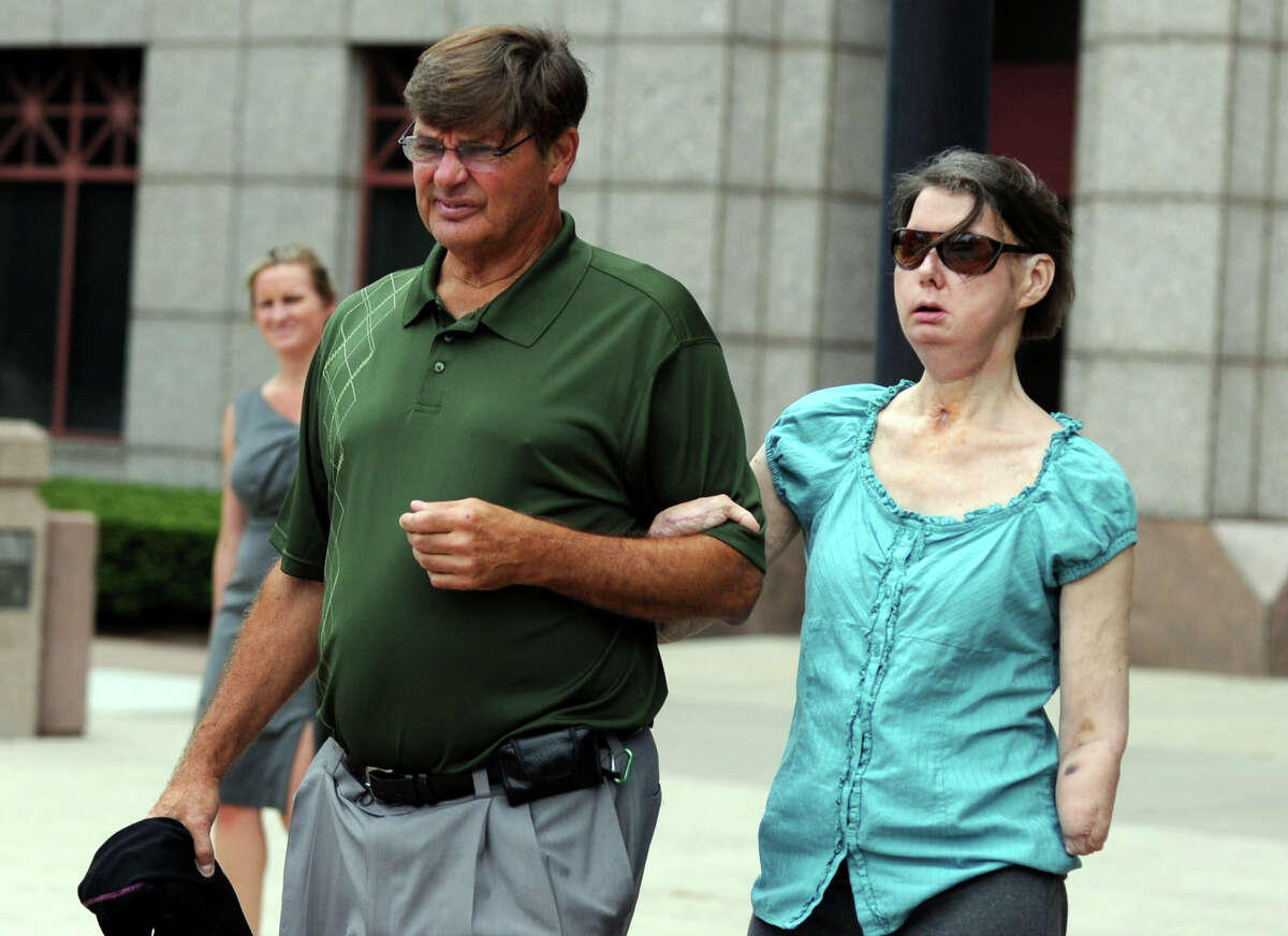 Charla Nash leaves the Legislative Office Building in Hartford, Conn., accompanied by her brother Steve Nash on Friday, August 10, 2012. Court documents obtained by the AP on Thursday Nov. 29, 2012 show a settlement between Nash's family and Herold's estate was approved by the Stamford Probate Court on Sept. 25 and the two sides met on Nov. 13 to finalize it.