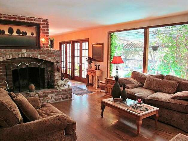 A raised hearth fireplace and floor-to-ceiling windows are highlights of the living room.