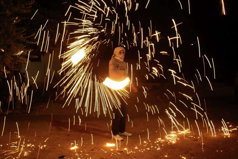 A Palestinian youth plays with fireworks while Palestinian Authority President Mahmoud Abbas speaks to the United Nations General Assembly at the UN headquarters in New York. Photo: Nasser Ishtayeh, STF / AP