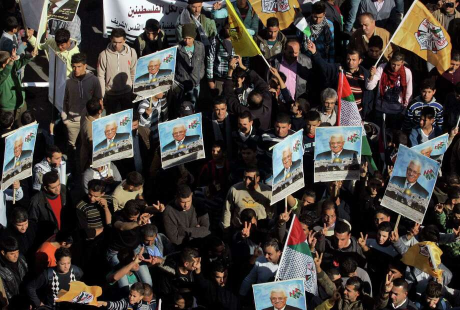 Palestinians hold pictures of President Mahmoud Abbas and wave Fatah flags during a rally supporting the Palestinian UN bid for observer state status, in the West Bank city of Nablus, Thursday. Photo: Nasser Ishtayeh, STF / AP