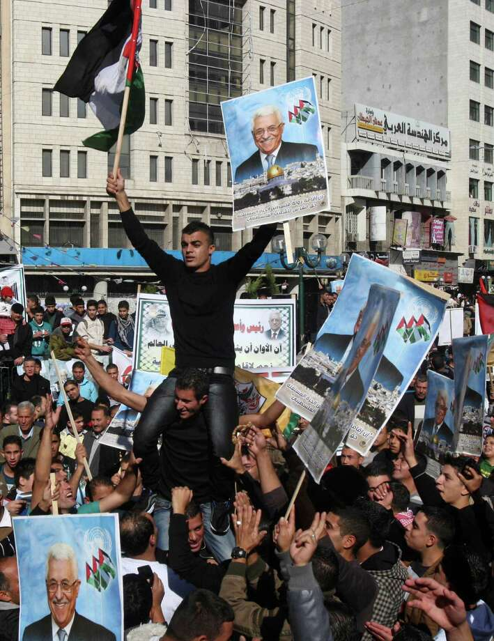 Palestinians hold pictures of President Mahmoud Abbas during a rally supporting the Palestinian U.N. bid for observer state status, in the West Bank city of Nablus. Photo: Nasser Ishtayeh, STF / AP