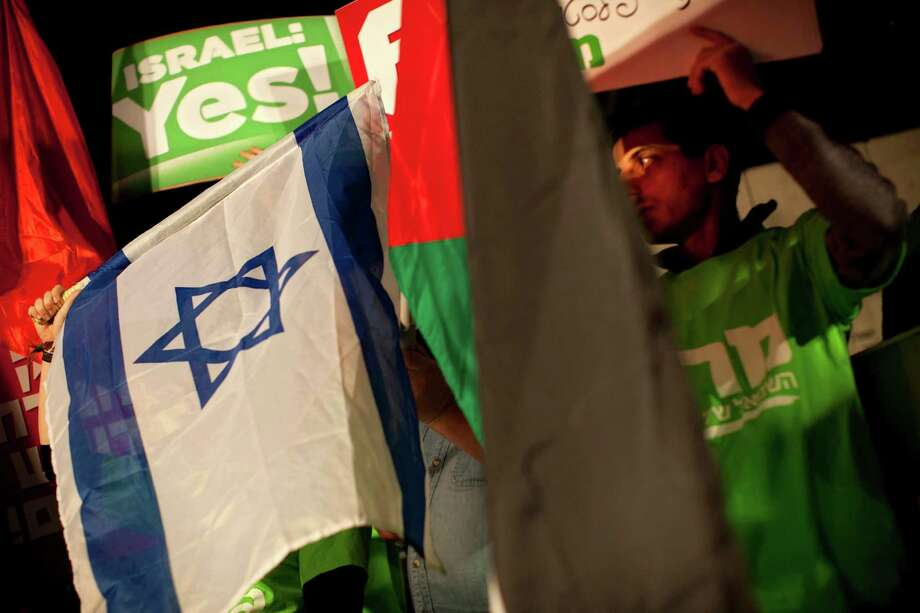Israeli left wing activists hold Israeli and Palestinian flags to support the Palestinian U.N. bid for observer state status, during a rally in Tel Aviv, Israel, Thursday. Photo: Oded Balilty, Associated Press / AP