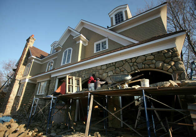 Stone masons Armando Lopez, left, and Efrain Cruz work on a large new home at the corner of South Benson and Judson Roads in Fairfield on Thursday, November 29, 2012. Photo: Brian A. Pounds / Connecticut Post