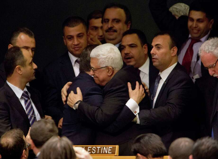 """President Mahmoud Abbas, center, of the Palestinian Authority is congratulated by Turkey's Minister of Foreign Affairs Ahmet Davutoglu at the United Nations General Assembly, Nov. 29, 2012. An overwhelming majority of countries voted on Thursday to recognize Palestine as a """"nonmember observer state"""" at the United Nations. Photo: DAMON WINTER, New York Times / NYTNS"""
