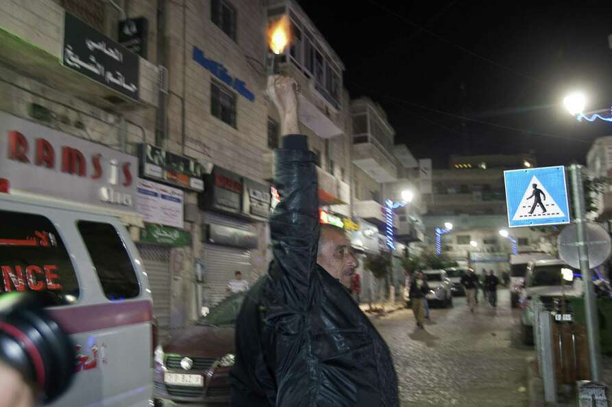 A Palestinian man fires a pistol in the air in celebration in the West Bank city of Ramallah. Despit