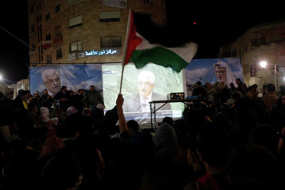 Palestinians wave Palestinian flags as they watch a large screen showing Palestinian President Mahmoud Abbas speaking to the United Nations. The resolution upgrading the Palestinians' status to a nonmember observer state at the United Nations was approved by the 193-member world body late Thursday by a vote of 138-9 with 41 abstentions. Photo: Majdi Mohammed, Associated Press / AP