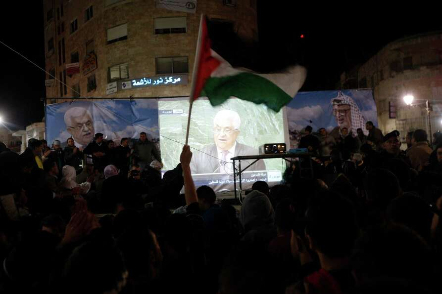 Palestinians wave Palestinian flags as they watch a large screen showing Palestinian President Mahmo