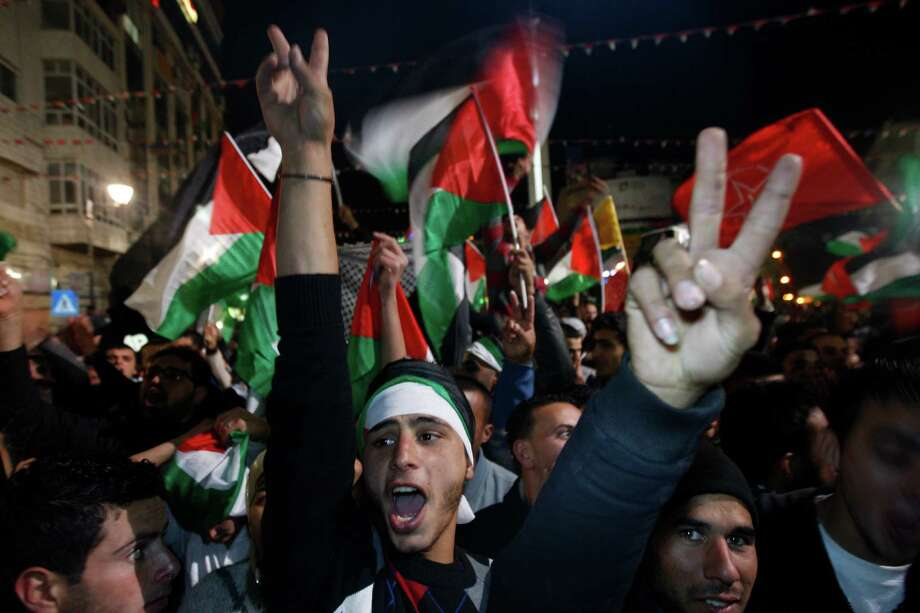 Palestinians celebrate as they watch a screen showing the U.N. General Assembly votes on a resolution to upgrade the status of the Palestinian Authority to a nonmember observer state, In the west bank city of Ramallah, Thursday, Nov. 29, 2012.  The U.N. General Assembly has voted by a more than two-thirds majority to recognize the state of Palestine. The resolution upgrading the Palestinians' status to a nonmember observer state at the United Nations was approved by the 193-member world body late Thursday by a vote of 138-9 with 41 abstentions. Photo: Majdi Mohammed, Associated Press / AP