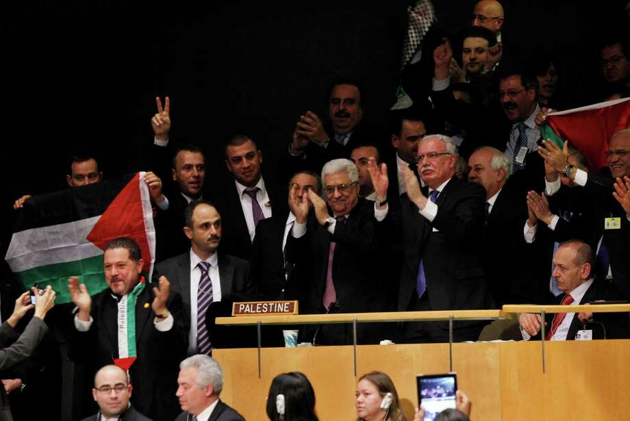 "Mahmoud Abbas, center, celebrates with members of his delegation and other supporters after the U.N. General Assembly's historic vote. Abbas had told the General Assembly that it was ""being asked today to 