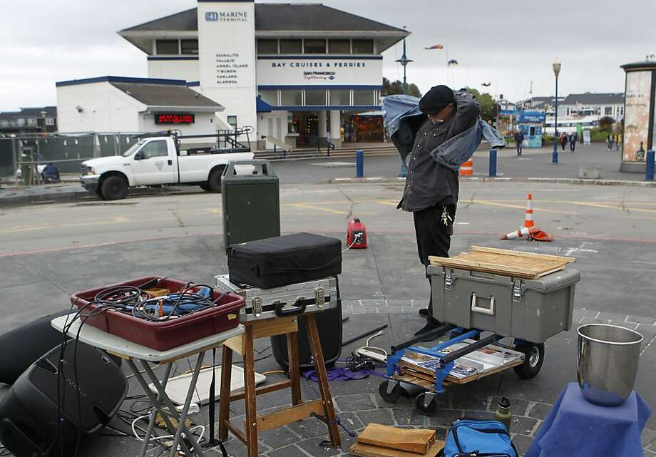 Blues musician Dave Earl packs it in before rain starts falling, but says the gray day's monetary effects are part of the business. Photo: Paul Chinn, The Chronicle
