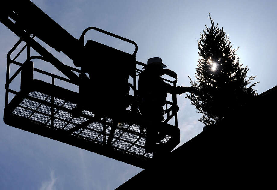 Felipe Lopez helps Michael Vassar, behind tree, install a Christmas tree on top of the uncompleted Victory Medical Center in Beaumont on Thursday. As part of a construction tradition, a tree is placed on the last beam installed in a building during the holidays. Work on the $21 million structure is expected to be done in the spring of 2013. Photo taken Thursday, November 29, 2012 Guiseppe Barranco/The Enterprise Photo: Guiseppe Barranco, STAFF PHOTOGRAPHER / The Beaumont Enterprise