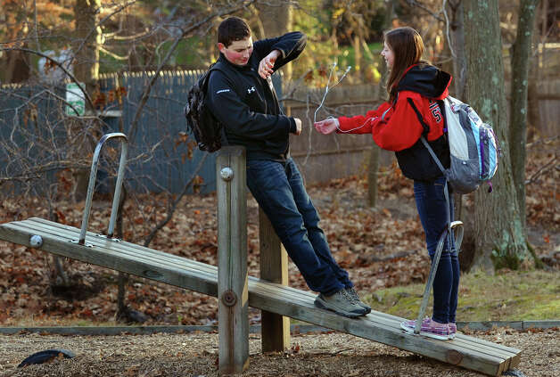 Fairfiel Warde students Sean Huban tries to fend off his friend and classmate Brittany Pond as she playfully hits him with her ear buds, while they hang out after school at the Owen Fish Playground in Fairfield, Conn. on Thursday November 29, 2012. Photo: Christian Abraham / Connecticut Post
