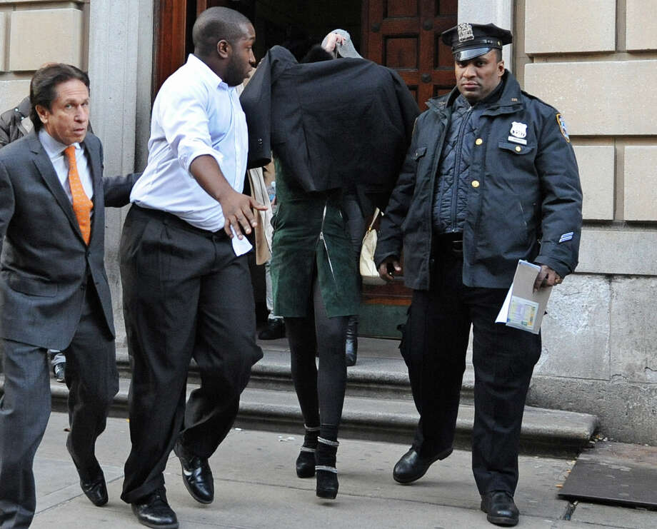 Lindsay Lohan, head covered, is escorted from a New York police station on Thursday. Photo: Louis Lanzano, FRE / FR77522 AP