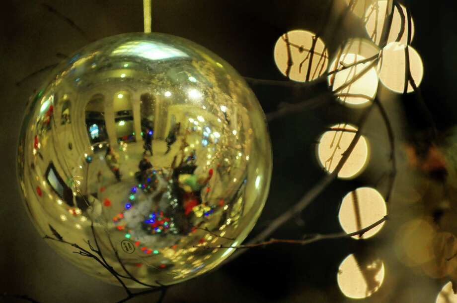 People in the rotunda of Albany city hall are reflected in a ornament on a tree decorated for the holiday on Thursday, Nov. 29, 2012 in Albany, NY.  (Paul Buckowski / Times Union) Photo: Paul Buckowski