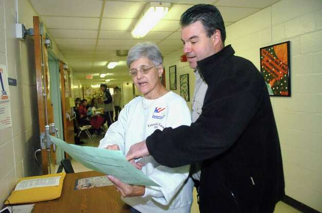 Randy Caravella, of Cos Cob, speaks with Theresa Linetti, an election official, at Central Middle School in 2007. Photo: Helen Neafsey, GT