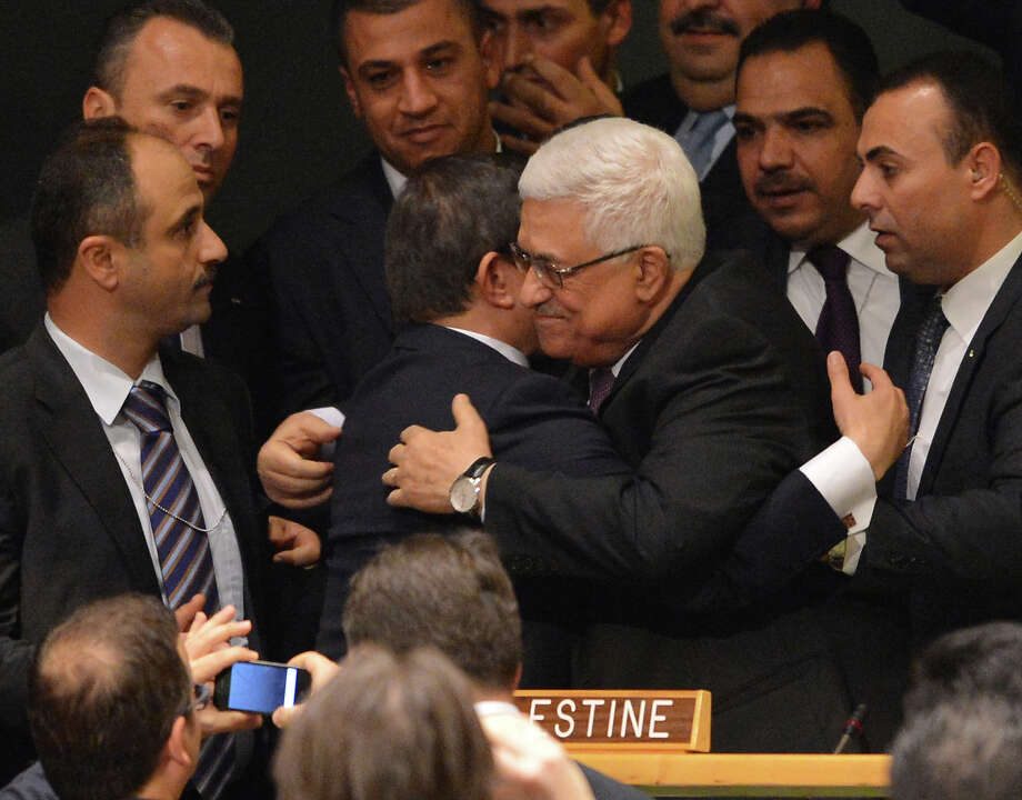 Palestinian Authority President Mahmoud Abbas (C) gets a hug from Ahmet Davutoglu, Turkey's Foreign Minister, as the Palestinians celebrate after the United Nations General Assembly voted to approve a resolution to upgrade the status of the Palestinian Authority to a nonmember observer state November 29, 2012 at UN  headquarters in New York. AFP PHOTO/Stan HONDA Photo: STAN HONDA, AFP/Getty Images / 2012 AFP