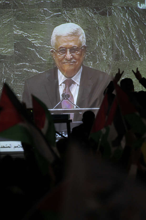 Palestinians watch on a giant screen Palestinian President Mahmoud Abbas speaking at the UN on November 29, 2012 in Ramallah. The UN General Assembly voted overwhelmingly to recognize Palestine as a non-member state, giving a major diplomatic triumph to president Mahmud Abbas despite fierce opposition from the United States and Israel. AFP PHOTO/ABBAS MOMANI Photo: ABBAS MOMANI, AFP/Getty Images / 2012 AFP