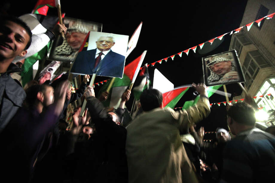 Palestinians celebrate  in the West Bank city of Ramallaha on November 29, 2012 after the General Assembly voted to recognise Palestine as a non-member state.  The UN General Assembly on Thursday voted overwhelmingly to recognize Palestine as a non-member state, giving a major diplomatic triumph to president Mahmud Abbas despite fierce opposition from the United States and Israel. AFP PHOTO / ABBAS MOMANI Photo: ABBAS MOMANI, AFP/Getty Images / 2012 AFP
