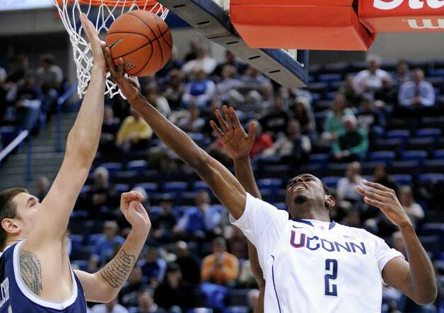 Connecticut's DeAndre Daniels, right is guarded by New Hampshire's Chris Pelcher during the first half of an NCAA college basketball game in Storrs, Conn., Thursday, Nov. 29, 2012. (AP Photo/Fred Beckham) Photo: Fred Beckham, Associated Press / FR153656 AP