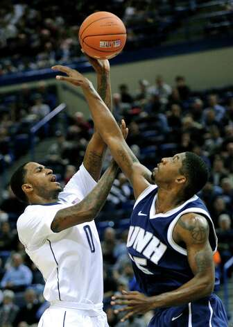 Connecticut's Phillip Nolan, left, shoots over New Hampshire's Ferg Myrick during the first half of an NCAA college basketball game in Storrs, Conn., Thursday, Nov. 29, 2012. (AP Photo/Fred Beckham) Photo: Fred Beckham, Associated Press / FR153656 AP