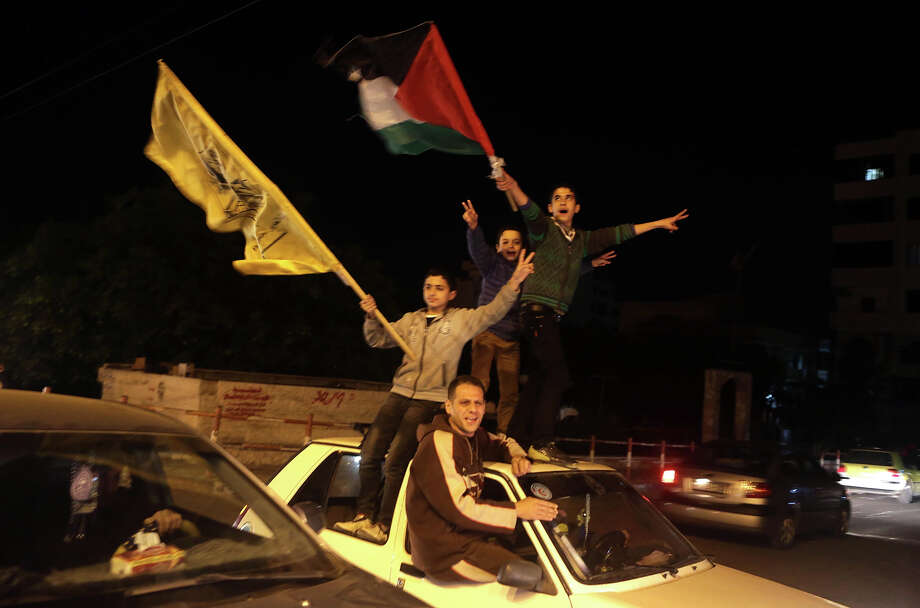 "Palestinians celebrate in Gaza City early on November 30, 2012, after the UN General Assembly voted to upgrade them to a non-member state observer.  The UN General Assembly on Thursday voted overwhelmingly to recognize Palestine as a non-member state, triggering scenes of joy on the streets of the Israeli-occupied West Bank.  In a major defeat for the United States and Israel, Palestinian president Mahmud Abbas won what he called a ""birth certificate"" for a Palestinian state, with the backing of 138 countries in the 193 member assembly.   AFP PHOTO / PATRICK BAZ Photo: PATRICK BAZ, AFP/Getty Images / 2012 AFP"