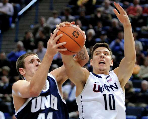 Connecticut's Tyler Olander, right, and New Hampshire's Chris Pelcher fight for a loose ball during the first half of an NCAA college basketball game in Storrs, Conn., Thursday, Nov. 29, 2012. (AP Photo/Fred Beckham) Photo: Fred Beckham, Associated Press / FR153656 AP
