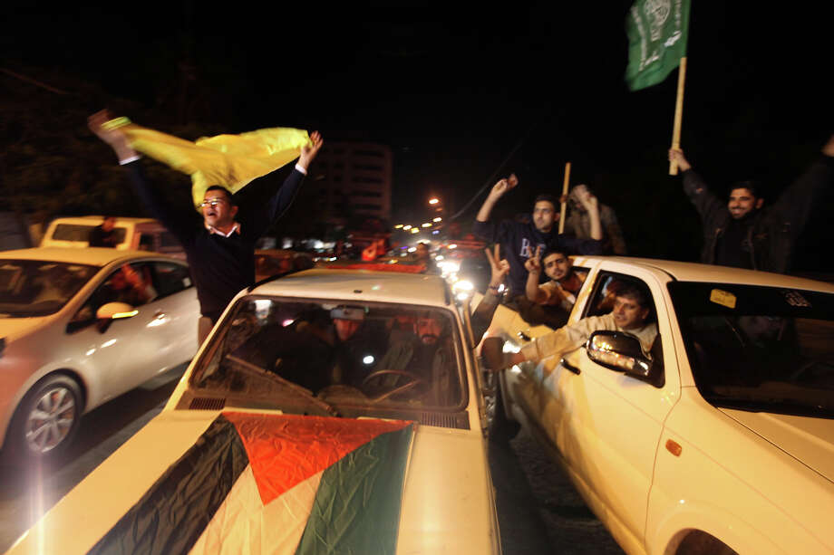 """Palestinian supporters of Fatah (L) and Hamas (R) celebrate together in Gaza City early on November 30, 2012, after the UN General Assembly voted to upgrade them to a non-member state observer.  The UN General Assembly on Thursday voted overwhelmingly to recognize Palestine as a non-member state, triggering scenes of joy on the streets of the Israeli-occupied West Bank.  In a major defeat for the United States and Israel, Palestinian president Mahmud Abbas won what he called a """"birth certificate"""" for a Palestinian state, with the backing of 138 countries in the 193 member assembly.   AFP PHOTO / PATRICK BAZ Photo: PATRICK BAZ, AFP/Getty Images / 2012 AFP"""